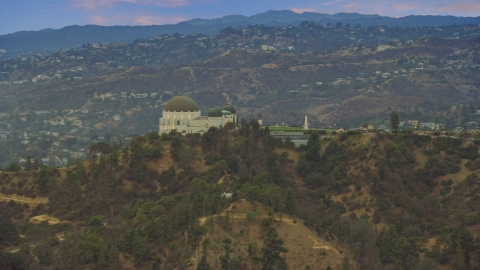 AX0158_006.0000241 - Aerial stock photo of Griffith Observatory at twilight against the hills, California