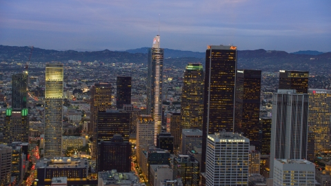 AX0158_047.0000110 - Aerial stock photo of Wilshire Grand Center and nearby skyscrapers at twilight in Downtown Los Angeles, California