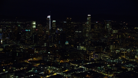 AX0158_093.0000359 - Aerial stock photo of The city skyline's tall skyscrapers at night in Downtown Los Angeles, California