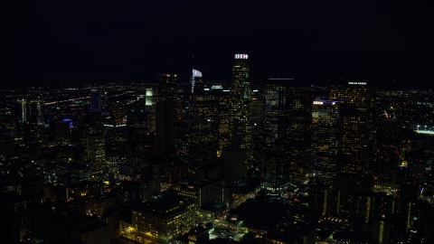 AX0158_110.0000136 - Aerial stock photo of Tall city skyscrapers at night in Downtown Los Angeles, California