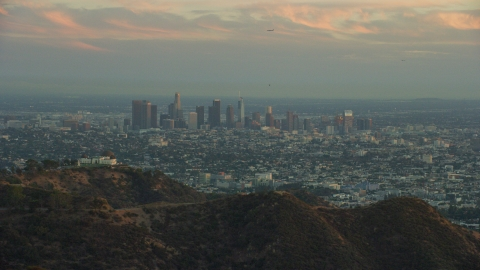 AX0162_105.0000154 - Aerial stock photo of The skyline of Downtown Los Angeles, California at twilight and Griffith Observatory