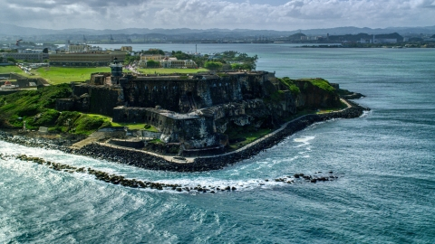 AX101_013.0000148F - Aerial stock photo of Historic fort along the coast of clear blue water, Old San Juan Puerto Rico