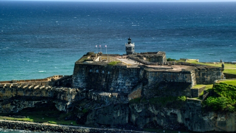 AX101_016.0000000F - Aerial stock photo of Historic fort along the coast resting on clear blue water, Old San Juan Puerto Rico
