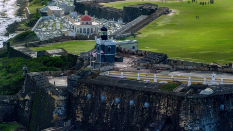 AX101_022.0000351F - Aerial stock photo of Historic fort and lighthouse on the coast, Old San Juan, Puerto Rico