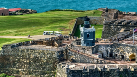 AX101_025.0000152F - Aerial stock photo of Historic fort and lighthouse in Old San Juan, Puerto Rico