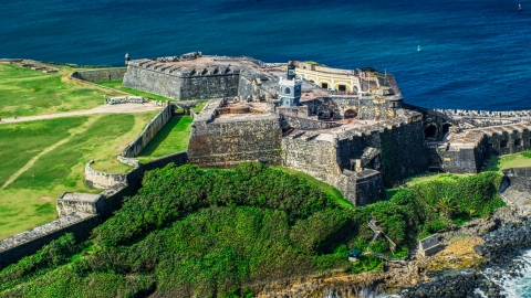 AX101_026.0000000F - Aerial stock photo of A historic fort and lighthouse beside blue waters, Old San Juan, Puerto Rico