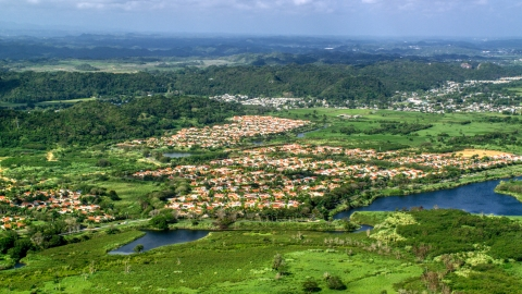 AX101_033.0000000F - Aerial stock photo of Rural neighborhoods among trees and grassy areas, Dorado, Puerto Rico