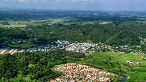 AX101_034.0000279F - Aerial stock photo of Rural neighborhood beside dense cluster of trees in Dorado, Puerto Rico