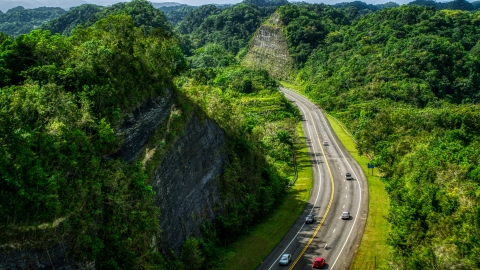 AX101_078.0000299F - Aerial stock photo of Light highway  traffic through lush green mountains, Karst Forest, Puerto Rico