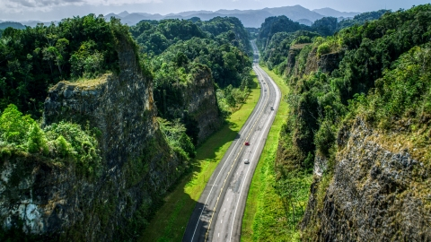 AX101_084.0000123F - Aerial stock photo of Light traffic on a highway through lush green mountains, Karst Forest, Puerto Rico
