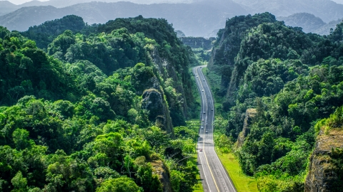 AX101_085.0000000F - Aerial stock photo of A highway cutting through lush green mountains, Karst Forest, Puerto Rico