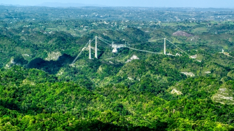 AX101_087.0000000F - Aerial stock photo of Arecibo Observatory rising above the lush green Karst Forest, Puerto Rico