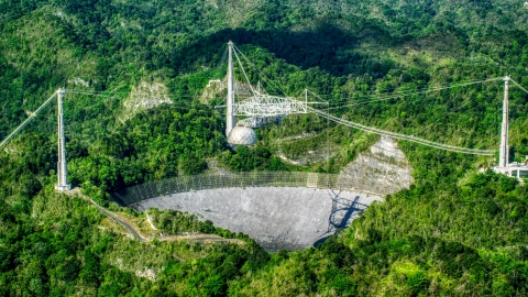 AX101_090.0000342F - Aerial stock photo of The dish of the Arecibo Observatory among lush green jungle, Puerto Rico