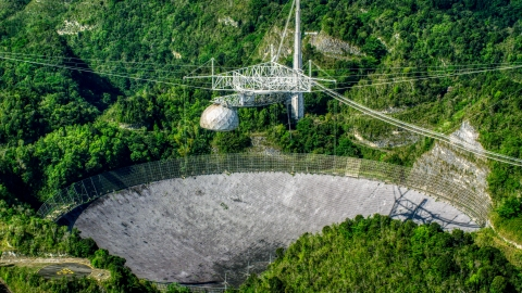 AX101_091.0000123F - Aerial stock photo of The Arecibo Observatory located in the lush green Karst forest of Puerto Rico