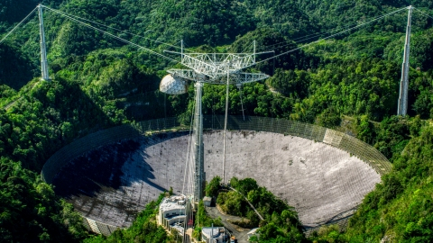 AX101_093.0000000F - Aerial stock photo of Arecibo Observatory in lush green Karst forest, Puerto Rico