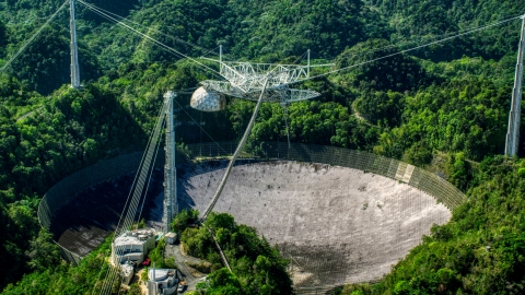 AX101_093.0000076F - Aerial stock photo of Arecibo Observatory in the green Karst forest, Puerto Rico
