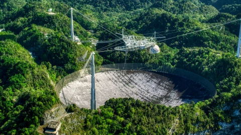 AX101_098.0000000F - Aerial stock photo of The Arecibo Observatory surrounded by trees, Puerto Rico