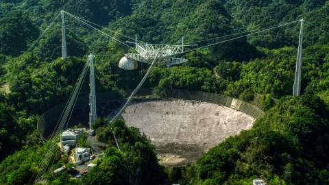 AX101_105.0000000F - Aerial stock photo of A view of the Arecibo Observatory surrounded by trees, Puerto Rico