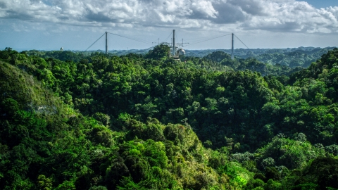 AX101_108.0000184F - Aerial stock photo of Arecibo Observatory seen from lush green mountains, Puerto Rico