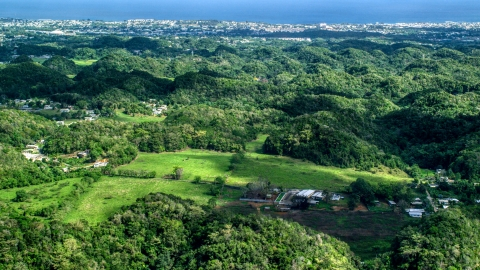 AX101_129.0000000F - Aerial stock photo of Tree covered hills and rural homes near the coast, Arecibo, Puerto Rico