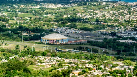 AX101_132.0000000F - Aerial stock photo of Coliseo Manuel Iguina sporting arena and homes, Arecibo, Puerto Rico