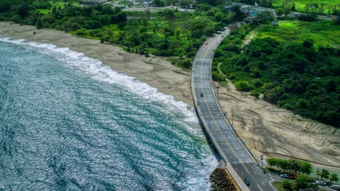 AX101_140.0000000F - Aerial stock photo of Coastal road cutting through trees and over a beach by blue water, Arecibo, Puerto Rico