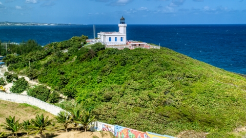 AX101_146.0000000F - Aerial stock photo of Arecibo Lighthouse on a hilltop by blue Caribbean waters, Puerto Rico
