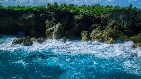 AX101_163.0000000F - Aerial stock photo of Coastal rock formations and caves, and crashing ocean waves in Arecibo, Puerto Rico