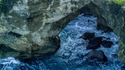 AX101_164.0000000F - Aerial stock photo of Water-filled sea cave on the coast, Arecibo, Puerto Rico