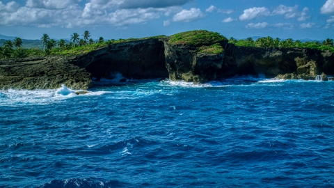 AX101_165.0000000F - Aerial stock photo of Coastal rock formation and crystal blue water, Arecibo, Puerto Rico