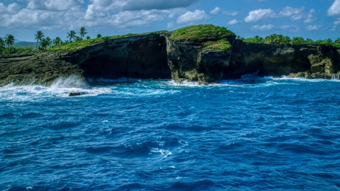 AX101_165.0000040F - Aerial stock photo of Rock formations on the rugged island coast and crystal blue water, Arecibo, Puerto Rico