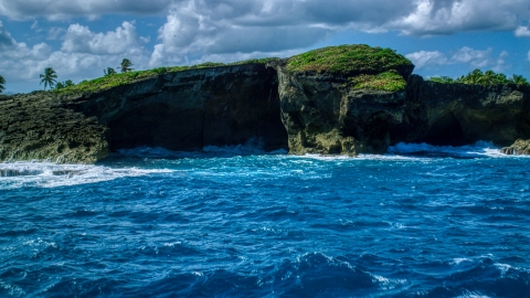 AX101_165.0000153F - Aerial stock photo of Rock formations on the rugged coast with crystal blue water, Arecibo, Puerto Rico