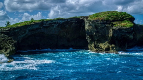 AX101_165.0000270F - Aerial stock photo of Crystal blue water and a shallow sea cave in Arecibo, Puerto Rico