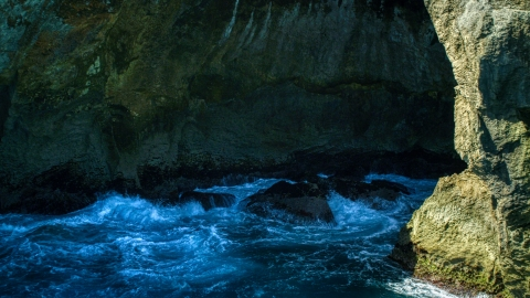 AX101_167.0000000F - Aerial stock photo of Churning water in a Caribbean sea cave, Arecibo, Puerto Rico
