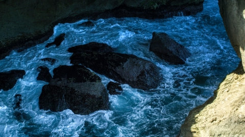 AX101_167.0000171F - Aerial stock photo of Churning water and rocks in a coastal sea cave, Arecibo, Puerto Rico