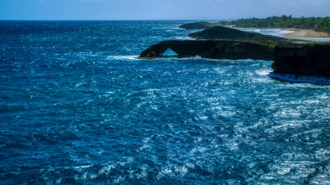 AX101_168.0000000F - Aerial stock photo of Arched rock formation in crystal blue water, Arecibo, Puerto Rico