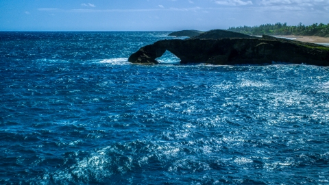 AX101_168.0000129F - Aerial stock photo of An arched rock formation in crystal blue water, Arecibo, Puerto Rico