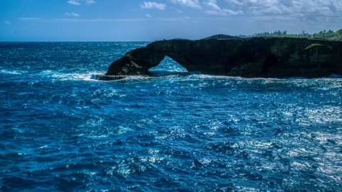AX101_169.0000000F - Aerial stock photo of Arched rock formation and blue waters, Arecibo, Puerto Rico