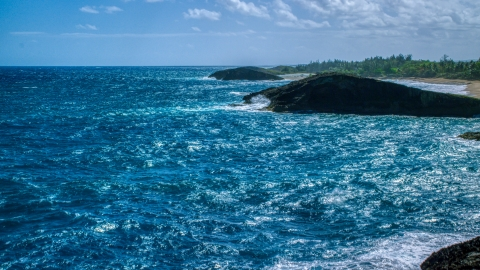 AX101_169.0000312F - Aerial stock photo of Domed rock formation in crystal blue waters, Arecibo, Puerto Rico