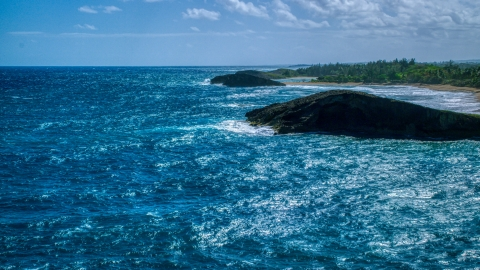 AX101_170.0000000F - Aerial stock photo of A pair of domed rock formations in crystal blue waters on the coast, Arecibo, Puerto Rico