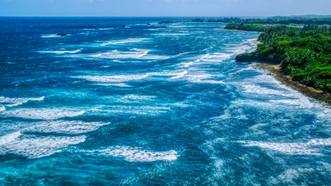 AX101_198.0000000F - Aerial stock photo of Ocean waves rolling toward a Caribbean island coast in Vega Baja, Puerto Rico