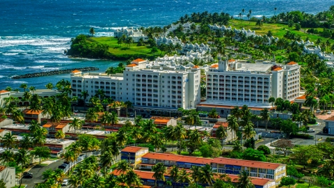 AX101_218.0000000F - Aerial stock photo of Caribbean island hotel and condo complex by the ocean in Dorado, Puerto Rico