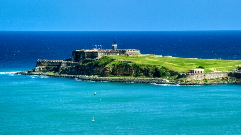 AX101_235.0000000F - Aerial stock photo of Fort San Felipe del Morro surrounded by crystal blue waters, Old San Juan, Puerto Rico