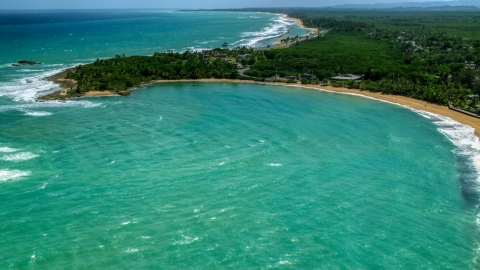 AX102_016.0000216F - Aerial stock photo of Clear turquoise waters by the beach and homes in Loiza, Puerto Rico