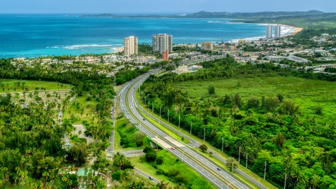 AX102_048.0000244F - Aerial stock photo of Highway 3 and a beach community with condo complexes in Luquillo, Puerto Rico