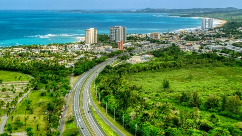 AX102_049.0000000F - Aerial stock photo of Beachside community and condos by crystal blue waters, Luquillo, Puerto Rico