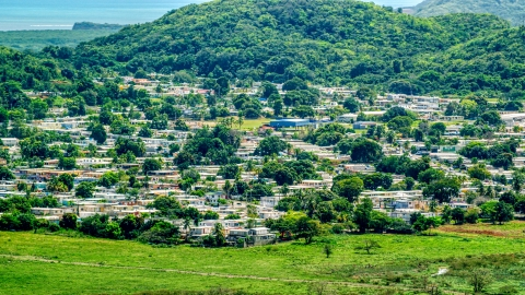 AX102_055.0000000F - Aerial stock photo of Homes beside tree covered hills, Fajardo, Puerto Rico