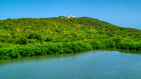 AX102_062.0000000F - Aerial stock photo of Cape San Juan Light, a hilltop lighthouse in Puerto Rico