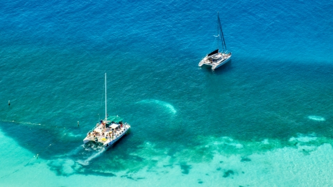 AX102_075.0000147F - Aerial stock photo of Catamarans in clear blue tropical waters, Rada Fajardo, Puerto Rico
