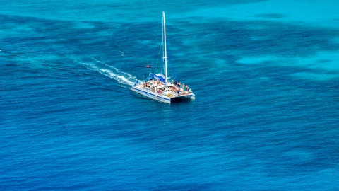 AX102_076.0000000F - Aerial stock photo of A catamaran in crystal clear blue tropical waters, Rada Fajardo, Puerto Rico